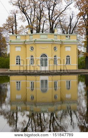 The building of the upper bath was built in the classical style yellow reflected in the water of the pond in the Park of Tsarskoe Selo Saint Petersburg Russia trees with multi-colored yellow orange green foliage overcast cloudy autumn