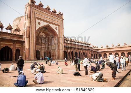 Fatehpur Sikri India - 2015 January 9 : The courtyard of the very important mosque Jama Masjid in Fatehpur Sikri with worshippers praying outside