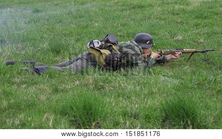 LENINGRAD REGION, RUSSIA - MAY 05, 2015: German infantryman lies in the grass. Reconstruction of the episode of the great Patriotic war