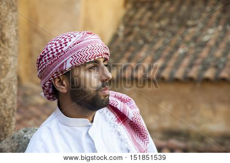 Young smiling handsome arabic man wearing traditional clothes