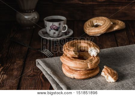Stacked Eclairs on the towel. Cup with the Beverage few eclairs and fork on background.