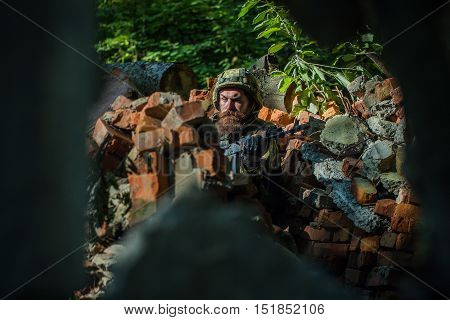 Young soldier with sad bearded face in military helmet and camouflage with gun on ruined bricks background in forest