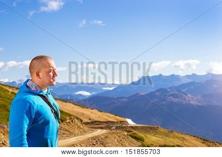 Young athletic man dressed in hoodie and white shorts admires of autumn mountain landscape views of hills and peaks of Caucasus mountains. Krasnaya Polyana - Alpine ski resort. Sochi Russia