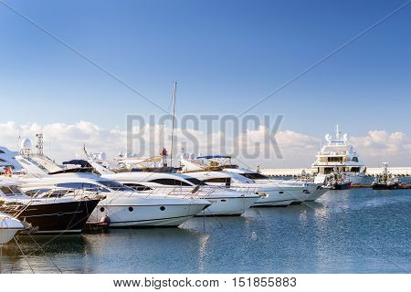 Luxury yachts and private boats moored at pier in Sochi seaport. In background the red warning lighthouse. Marine station complex Port. Krasnodarskiy kray Russia