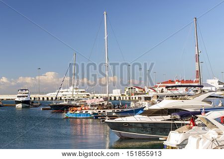 Luxury yachts and private boats moored at pier in Sochi seaport. In background is concrete promenade and Black sea. Marine station complex Port. Krasnodarskiy kray Russia