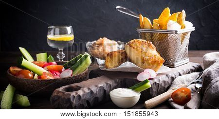Fish and chips. Fried fish fillet with homemade baked potatoes and fresh salad on wooden cutting board.