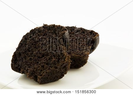 Rich and moist chocolate muffin sliced in half on white plate. Delicious sweet food background.