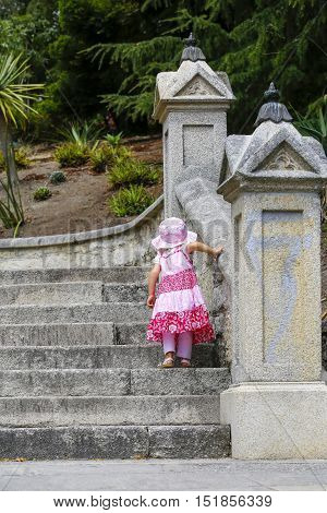 Little girl in pink dress looking walking upstairs . Staircase lead to to Christ Church Cathedral in Nelson, New Zealand.