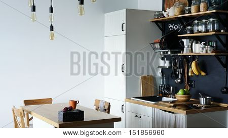 The design of the modern home kitchen in the loft-style and rustic. black wall with shelves trays jars mugs sink .