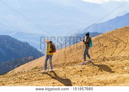 Sochi Russia - October 31 2015: Sweet young girl makes selfie with action-camera on background of autumn mountain landscape. Nearby is a sports boy. Views of hills and peaks of Caucasus mountains. Krasnaya Polyana - Alpine ski resort. Rosa Khutor Sochi Ru