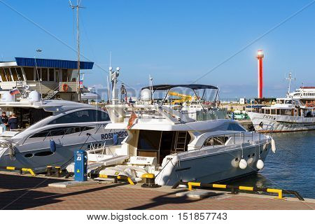 Sochi Russia - November 1 2015: Luxury yachts and private boats moored at pier in Sochi seaport. In background the red warning lighthouse. Marine station complex Port. Krasnodarskiy kray Russia