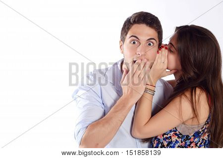 Portrait of a young woman whispering secret to her boyfriend. Isolated white background.