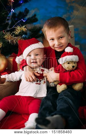 Portrait Of Happy Children With Christmas Gift Boxes And Decorations. Two Kids Having Fun At Home