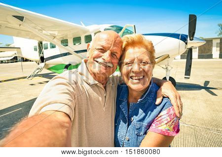 Senior happy couple taking selfie with private ultralight plane for tour around the world - Active elderly concept with retired people enjoying pension moments - Bright sunny afternoon color tones