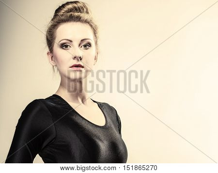 Portrait of young beautiful girl blonde woman makeup and hair bun gray background