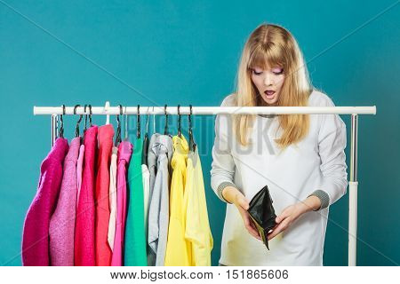 Pretty woman looking into empty wallet want clothing from wardrobe. Young undecided shopper girl making suprised face. Shopaholic concept.