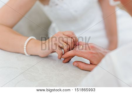 Bride and groom holding hands. Bride and groom holding hands. Wedding rings close up. Hands on the table.
