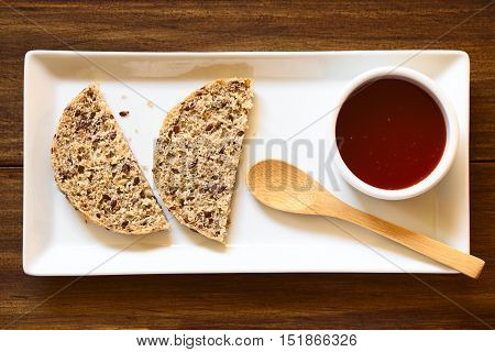 Homemade rose hip jam and wholegrain rolls on plate with small spoon photographed overhead with natural light