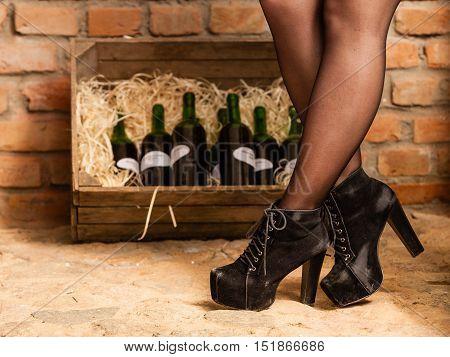 Female Legs And Wine Bottles In Cellar
