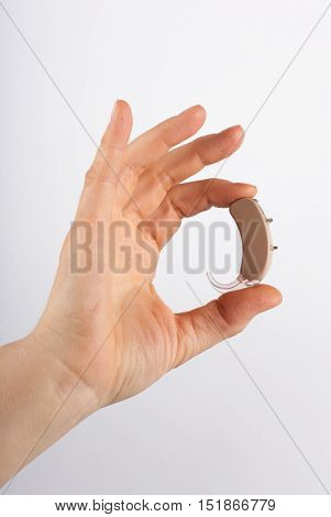 A Hand showing a hearing aid with white background