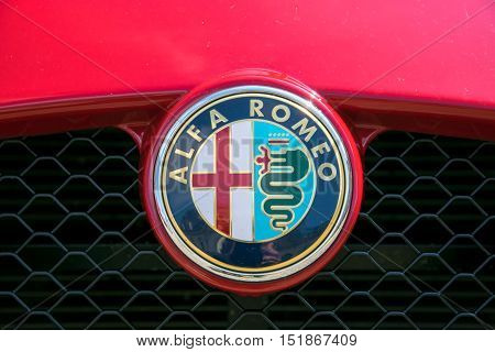 TURIN, ITALY - JUNE 9, 2016: Closeup of the Alfa Romeo logo on the hood of a red car model