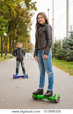 Young  Woman Riding Hoverboard - Electrical Scooter, Personal Eco Transport. On  Background Of  Boy