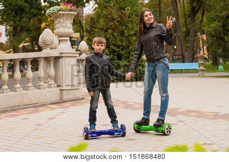 A Young  Mom And Son Riding Hoveboard Personal Eco Transport.