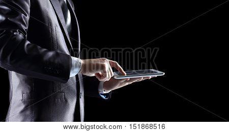 businessman working on digital tablet. photo on black background