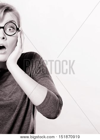 Feelings tension astonishment adrenaline concept.S hocked lady expressing awe. Young girl in glasses holding her face showing strong emotions.