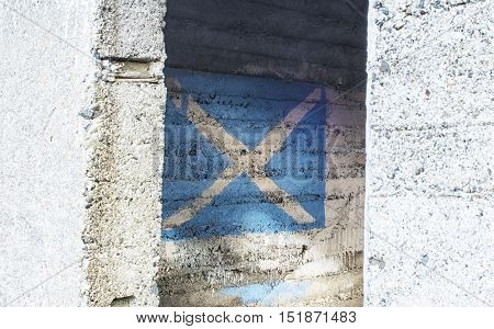 Looking into old abandoned concrete building with Scottish flag of St Andrews Cross painted on wall