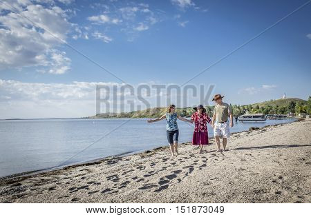 little old senior lady flanked by her daughter and son holding hands walking and talking along the beach with lake in the background.
