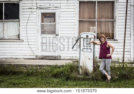 horizontal image of a woman modelling in front of an old vintage gas pump with an old building in the background in the summer time