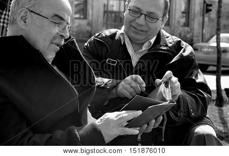 Istanbul Turkey - March 10 2013: Nostalgic Old Photo Album Memories. In a park looking at the old man two old photo albums.