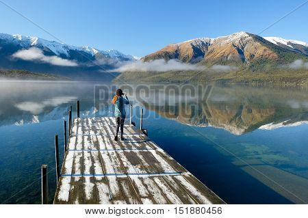 A Woman on A Dock Photographing an Alpine Lake Reflection.  Nelson Lakes National Park, Southern Alps, New Zealand.