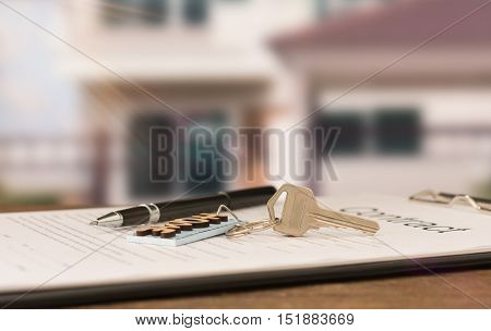 closeup house key on contract document with house key in house background.