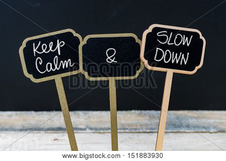 Keep Calm And Slow Down Message Written With Chalk On Mini Blackboard Labels