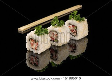 White beaters and sticks for sushi on black acryle with reflection