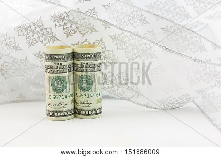 Elegant fresh American financial investment reflected in pair of dollar currency in front of swirl of white ribbon. Horizontal image is symbolic of success and new initiatives.
