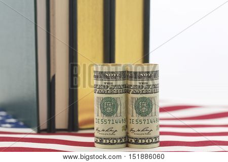 Pair of American dollars on an American stars and stripes flag pattern. National policy on costs of education needed.