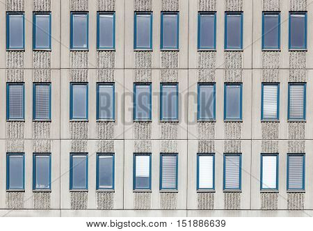 Elongated narrow windows in three rows of grooved concrete facade.