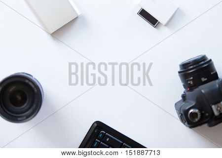 White desk with a professional camera and accessoires on it. Top view, copy space