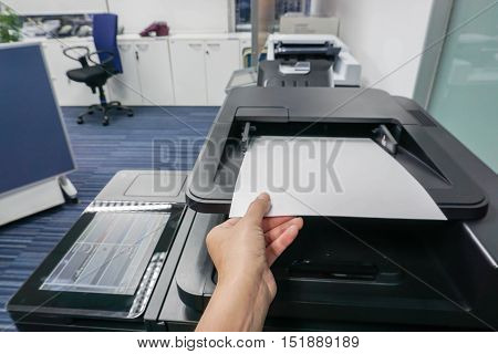 Businesswoman put paper sheet into printer machine