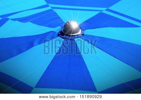 Detail of the top of a blue beach umbrella (sunshade - parasol) with sparkles