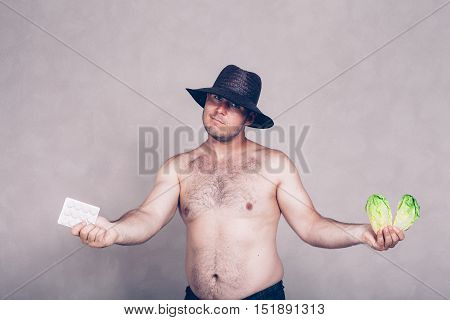 Naked corpulent man in hat giving pharmaceutical products and lettuce.