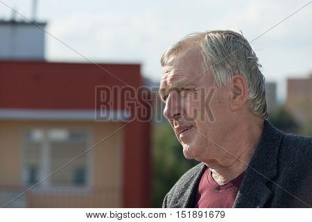 Closeup of senior man and building urban background.