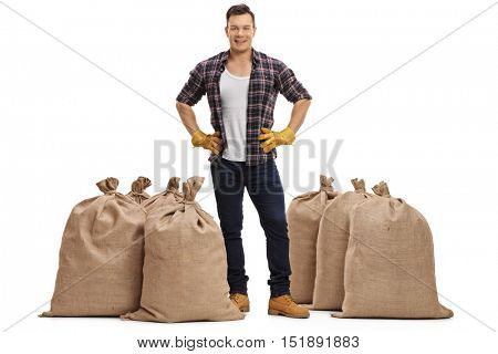 Full length profile of a male farmer standing between burlap sacks isolated on white background