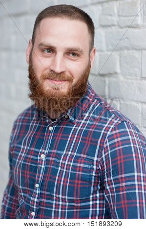 portrait of young bearded man wearing flannel shirt in front white brick wall