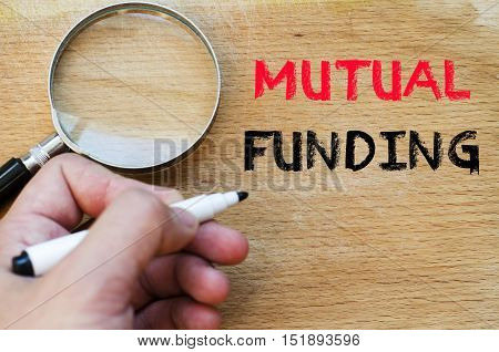 Human hand over wooden background and mutual funding text concept