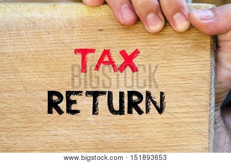 Human hand over wooden background and tax return text concept