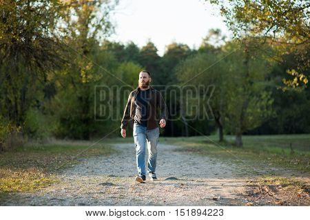 serious bearded young man walking in the park with a confident stride